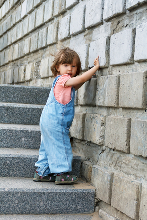 Baby girl in blue clother goes down on the stairs