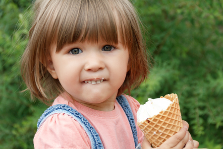 Horizontal photo of cute girl are eating icecream in summer time Stock Photo