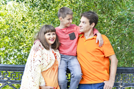 Happy family pregnant mother father and son looking to each others Stock Photo