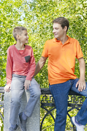 Man and boy are talking looking to each others in summer