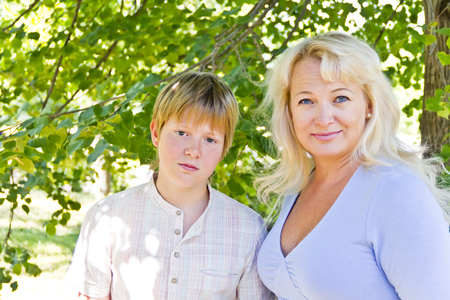 crone: Blond woman and son smiling under green crone of tree in summer