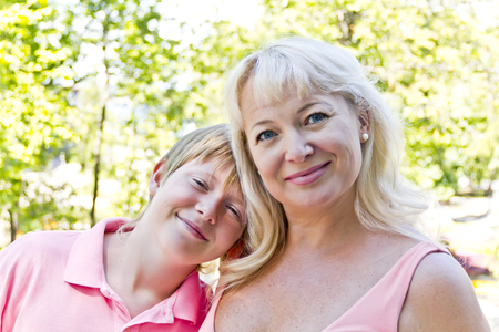 Portrait of woman with son in pink on green Stock Photo