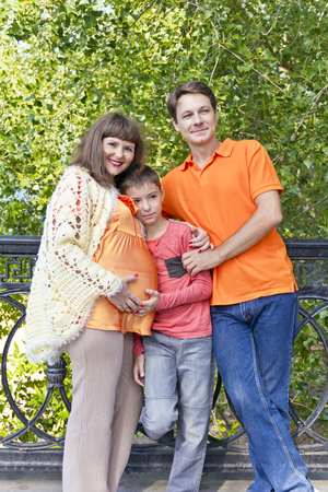 Happy family with pregnant mother in summer embankment Stock Photo