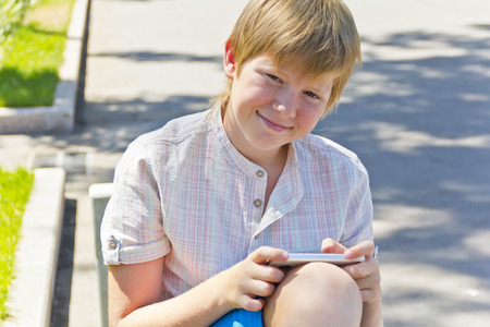 Blonde smiling boy with cellular phone in summer