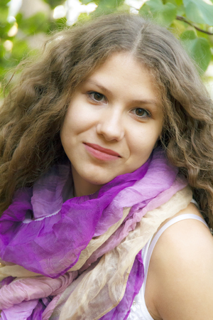 Young beautiful girl with curly hair in purple scarf photo