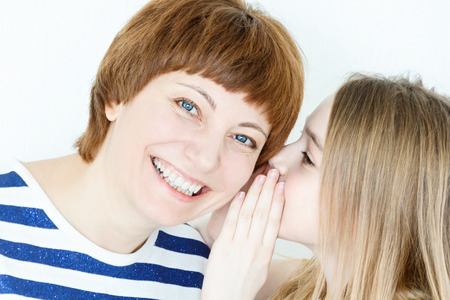 Daughter says a secret an her mother ear on white wall