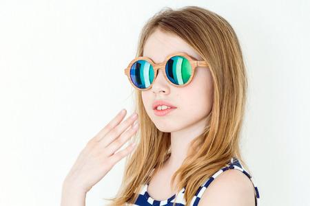 Portrait of  blond girl in green sunglasses on white