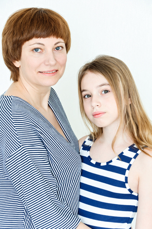 thirteen: Portrait of happy mother and daughter near white wall
