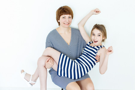 Playing family mother holds an adult daughter in her arms Stock Photo