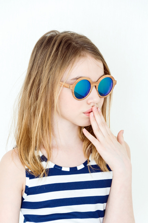 Cute girl eleven years old  in green sunglasses on white  Stock Photo