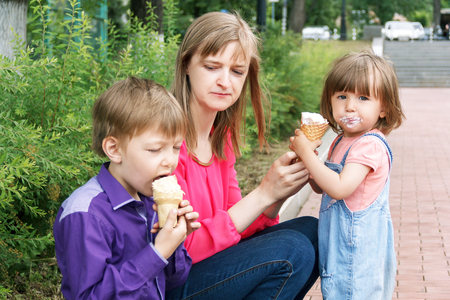 Mother with boy and baby girl sitting in summer park eating icecream photo