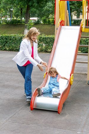 Mother with baby girl riding on hutches with screw up one eyes photo