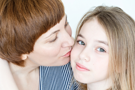 Portrait of kissing mother and daughter on white
