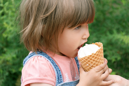 Horizonta photo of cute girl are eating icecream in summer time photo