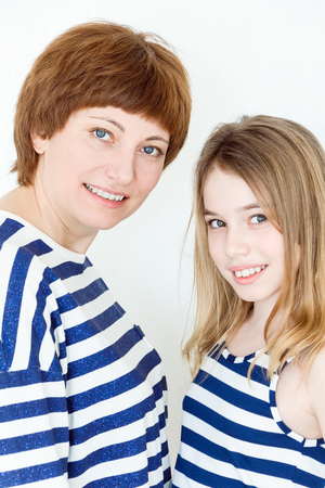 Portrait of happy mother and daughter near white wall