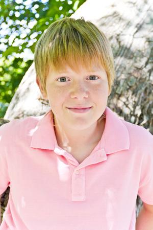 Portrait of cute blond boy in a pink shirt