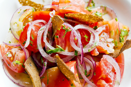 Colorful salad with red tomato onions and bread