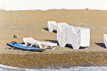 Empty beach with sun loungers and surfboard in summer day Stock Photo