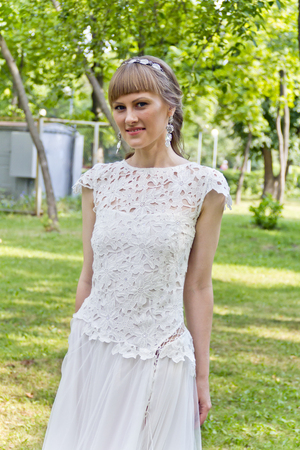 Beautiful bride in white lace dress of the summer park