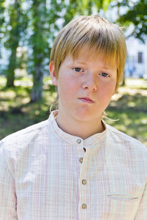 Portrait of serious boy in a white shirt in park Stock Photo