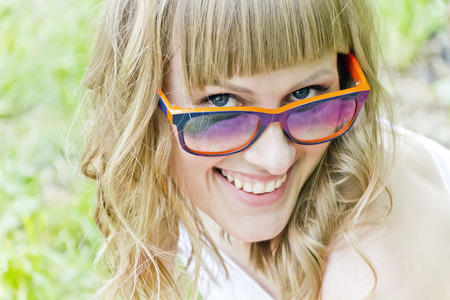 Portrait of smiling girl with orange sunglasses Imagens