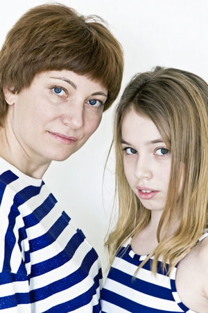 Mother and daughter playing with blond long hair near white wall