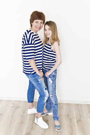 Happiest mother and daughter near white wall in striped clothes Stock Photo