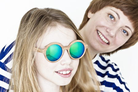 Mother and daughter in green sunglasses playing near white wall Stock Photo