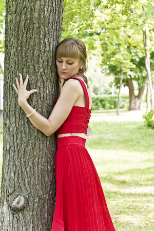 Beautiful lady in red are standing near tree summer day Imagens