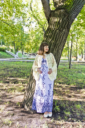 Pregnant woman with brown hair near tree in park Stock Photo