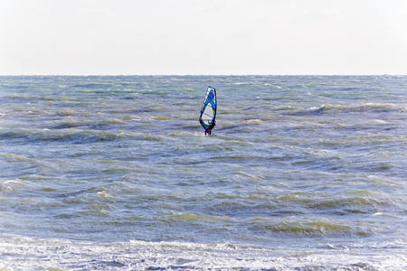 Horizontal photo of surfer in open choppy sea