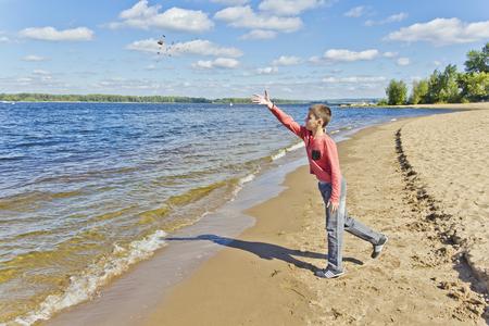 Junge in Rosa werfen Sand auf einen Strand an der Böschungsseite Standard-Bild
