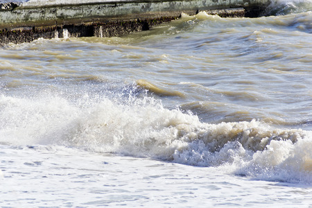 Sea waves with foam are breaking on the breakwater Stock Photo