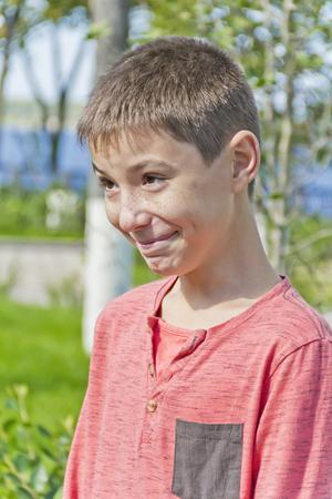 Vertical portrait of smiling teenager boy in pink