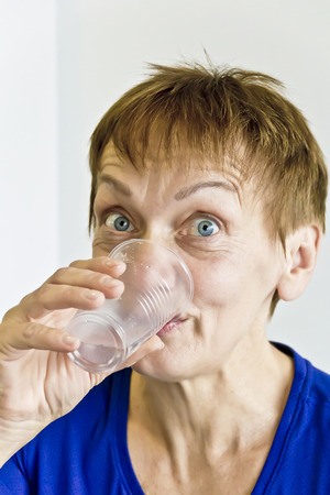 Elderly woman with short haircut are drinking a water