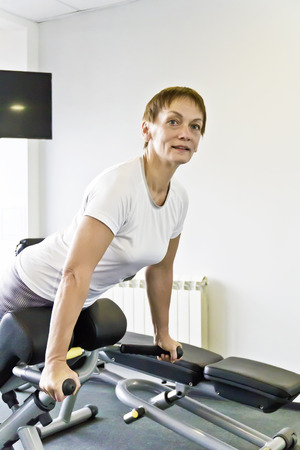 Smiling elderly woman with a short haircut in the gym