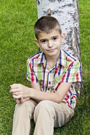 Cute brunette boy eleven years old sitting near tree Standard-Bild