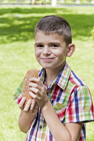 Cute brunette boy eating hotdog with appetite Banque d'images