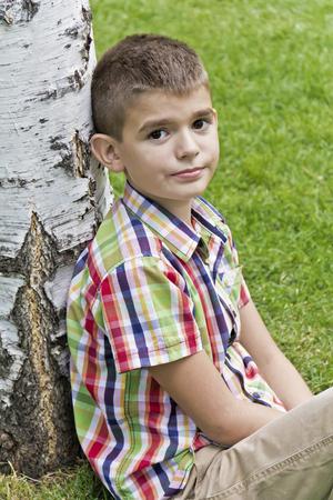 Cute brunette boy eleven years old sitting near tree