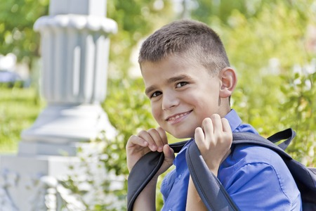 Brunette boy are smiling with school backpack Stock Photo