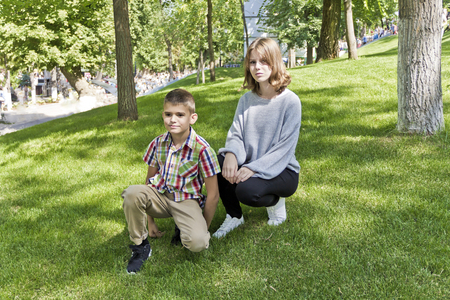 Brother and sister are sitting on green grass in park