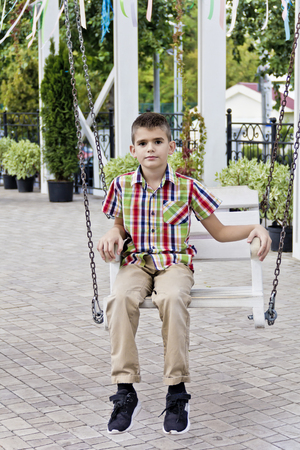 Cute brunette boy ride on a swing in summer