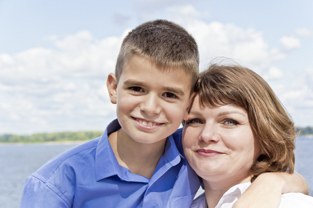 Happiest mother and son on river background in summer