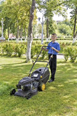 Cute smiling boy are working with lawn mower in summer