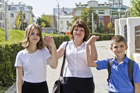 Happiest mother with daughter and son walking in summer