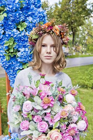 Portrait of cute blond girl fourteen years old in flowers wreath