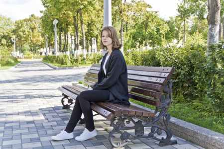 Beautiful girl fourteen years old are sitting on the bench