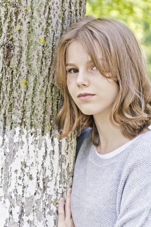 Beautiful girl fourteen years old lean against tree