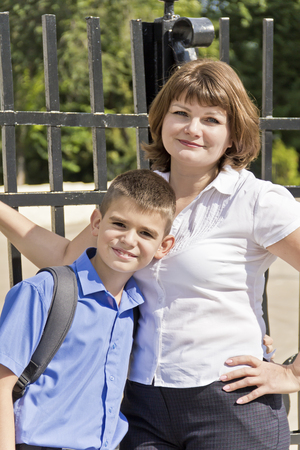 Happiest mother and son near fence in summer time Stock Photo