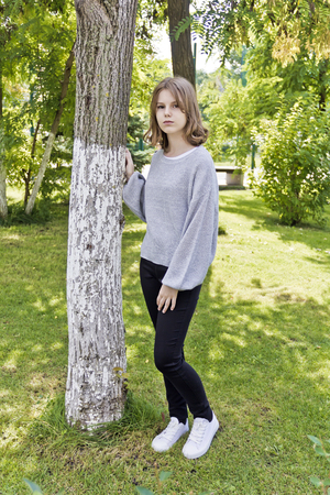 Beautiful girl fourteen years old lean on the tree